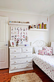 Shabby chest of drawers and blackboard with alphabet next to the bed in the nursery