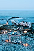 Romantisches Picknick mit Windlichtern, Laternen, Liege und Kissen am Meer