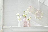 White ranunculus in glass bottles wrapped in cord and wreaths of flowers hung from silk ribbons