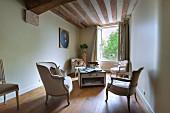 Loungebereich mit antiken Sesseln vor offenem Fenster unter rustikaler Holzbalkendecke