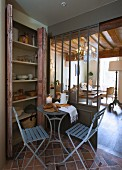 Bread on bistro table and two folding chairs in front of cupboard and view of chandelier in living area