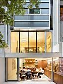 Moderne Glasfassade und Einblick in beleuchteten Wohnraum mit Familie am Esstisch