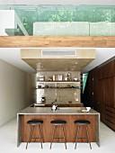 Blick auf Kücheninsel mit filigranen Barhockern und Galerie mit Glasbrüstung