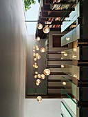View from below up stairwell with illuminated spherical pendant lamps and glass balustrade panels
