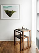 Elegant minimalist desk and chair next to window and framed modern artwork on wall