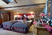 Lit table lamps and Christmas presents in cosy chalet bedroom