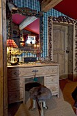 Rustic dressing table and stool made from stuffed animal parts below mirror on wall