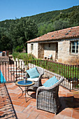 Wicker armchairs on terrace of Mediterranean country house with pool