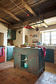 Island counter in Mediterranean kitchen with distressed blue and red cabinets