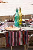 Colourful bottles and striped tablecloth on set table