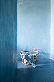 Basket of blue textiles on blue floor against blue wall