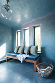 Blue cushions on wooden bench below three narrow windows in blue interior