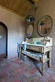 Old console table converted into vintage washstand below oval mirrors