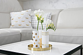 Elegant hand-made vases on golden tray on coffee table