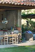 Wooden table on roofed terrace in Mediterranean garden