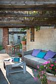 Korbmöbel und Holztisch auf überdachter Terrasse