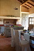 Dining table and loose-covered chairs in Mediterranean country-house kitchen