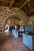 Open-plan interior in old Mediterranean house with stone arch