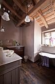 Nostalgisches Bad mit antiken Möbeln unterm offenen Dach mit Balken