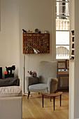 Grauer Polstersessel mit Katze, Stehlampe und Beistelltisch in Altbauwohnung