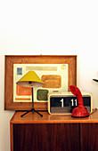 Retro Radio, Telefon, Tischlampe und gerahmtes Bild auf Kommode