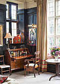 Antique bureau against black panelled wall and below lattice window