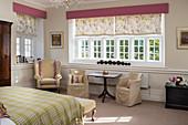 Romantisches Schlafzimmer mit Sitzgruppe vor dem Sprossenfenster