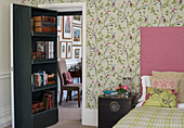 Bookcase on concealed door leading into romantic bedroom