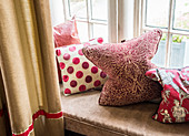 Cushions with various red-patterned covers on windowseat