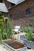 Terrasse mit Teich und Pflanzkübeln vor einem altem Steinhaus