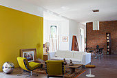 Yellow wall and artistic mixture of furnishings in open-plan interior