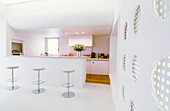 Bar stools in open-plan kitchen of futuristic architect-designed house