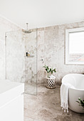 Freestanding bathtub and shower with glass partition in elegant bathroom with limestone tiles