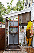 Vintage outdoor shower, surfboard leaning against wall