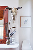 Mirror, vase with feathers and candle holder on white shelf, animal skull above