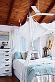 Doppelbett mit Baldachin und Vintage Kommode im Schlafzimmer mit Holzdecke