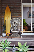 Surfboard, peacock chair and swing on vintage porch of a wooden house