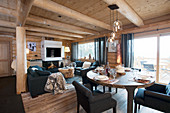 Modern furniture in living and dining room of log cabin