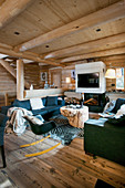Modern furniture in cosy living room of log cabin