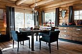 Gedeckter Tisch mit Polsterstühlen im winterlichen Blockhaus
