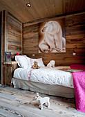 Eisbär-Bild über dem Bett im Kinderzimmer mit Holzwänden