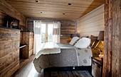 Rustic bedroom with wood panelling and log-cabin ambiance