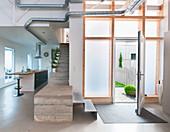 Open front door leading into industrial-style kitchen