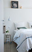 View into white bedroom through open door