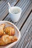 Cup of coffee and bowl of pastries on wooden boards