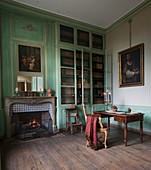 Open fireplace and green wood panelling in historical library