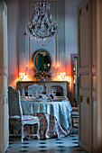 View through open double doors to set table in candlelit room