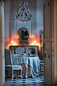 Blick durch offene Doppeltür auf gedecktem Tisch bei Kerzenlicht