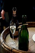 Open bottles and glass of Champagne on top of wooden barrel