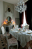 Festively set table in historical dining room with fireplace